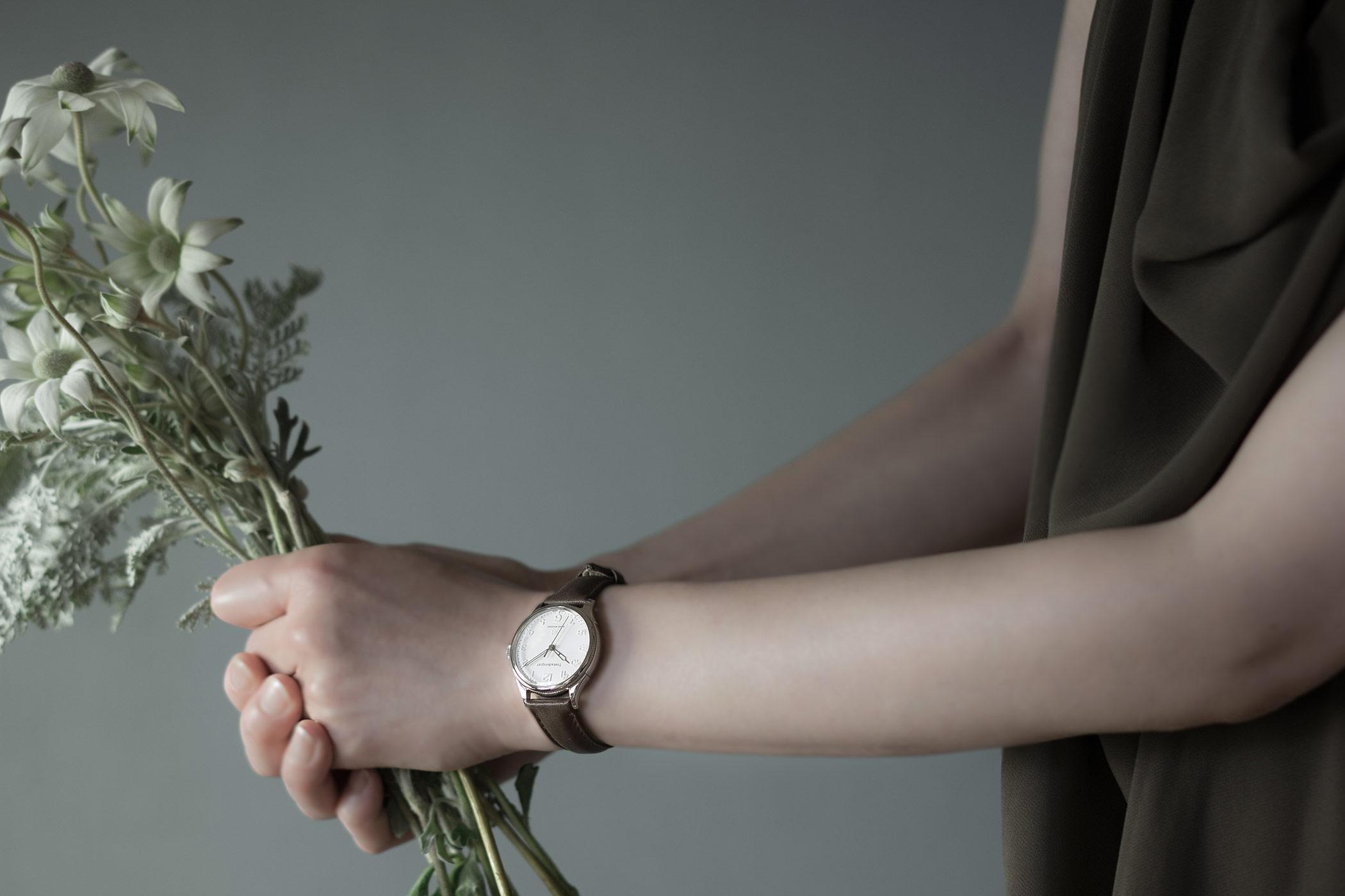 Nel(ネル)ダークブラウンを着用し、フランネルフラワーの花束を差し出す女性