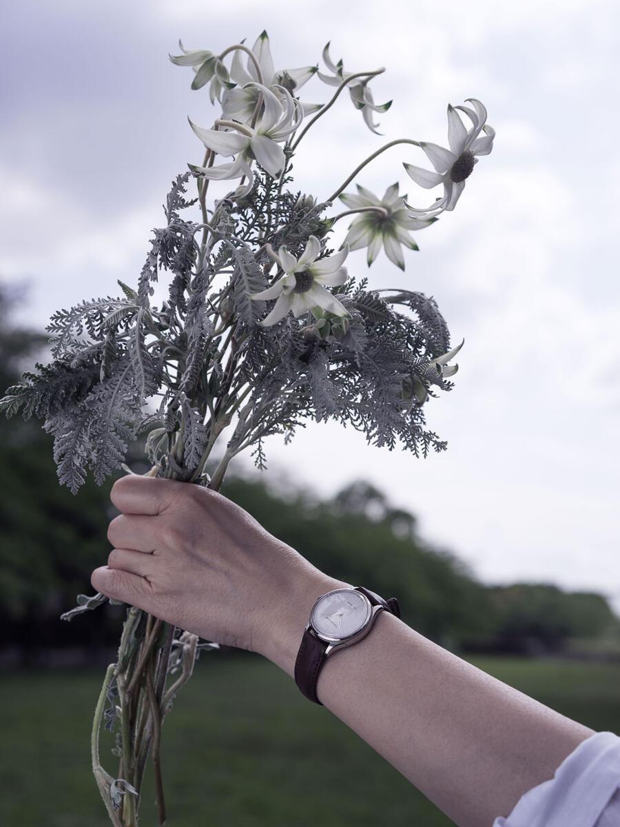 女性が花束を空に掲げる姿